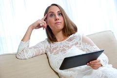 Mujer atractiva con la tableta en casa imagen de archivo libre de regalías