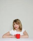 Mujer atractiva con la taza roja Foto de archivo libre de regalías