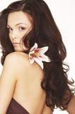 Mujer atractiva con las flores blancas brillantes. foto de archivo