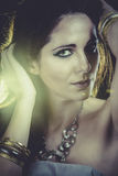 Mujer atractiva con las pulseras del oro y de la plata sobre luz de oro Fotografía de archivo