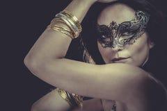 Mujer atractiva con las pulseras venecianas de la máscara y del oro y de la plata Fotografía de archivo libre de regalías