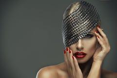 Mujer atractiva con los labios y la decoración rojos del metal fotografía de archivo