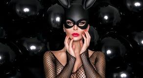 Mujer atractiva con los pechos grandes, llevando un conejito de pascua negro de la máscara imagen de archivo