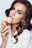 Mujer atractiva con maquillaje de la belleza que come el helado Imagen de archivo libre de regalías