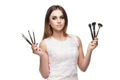 Mujer atractiva con un sistema del cepillo para el maquillaje en las manos Imagen de archivo