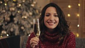 Mujer atractiva con un vidrio de champán que mira la cámara en fondo del árbol de navidad Ella aumenta el vidrio almacen de video