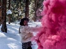 Mujer atractiva con una granada de humo colorida foto de archivo