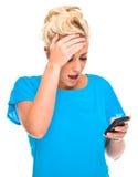Mujer atractiva dada una sacudida eléctrica por el mensaje del teléfono celular Imagen de archivo libre de regalías