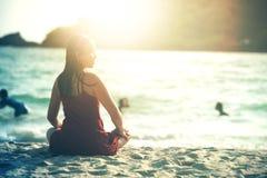 Mujer atractiva de Asia que se sienta y que presenta en la arena de la playa fotos de archivo