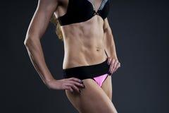Mujer atractiva de la aptitud en fondo gris en estudio Primer muscular del abdomen Fotografía de archivo