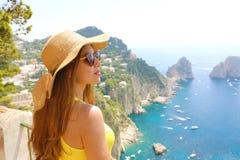 Mujer atractiva de la moda con las gafas de sol y el sombrero de paja que disfruta de la vista de Capri de la terraza, isla de Ca foto de archivo