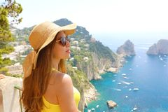 Mujer atractiva de la moda con las gafas de sol y el sombrero de paja que disfruta de la vista de Capri de la terraza, isla de Ca foto de archivo libre de regalías