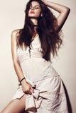 Mujer atractiva de la moda del encanto con la piel bronceada, pelo flojo, igualando maquillaje en un vestido del verano y una rop Imagen de archivo libre de regalías