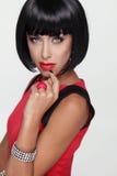 Mujer atractiva de la morenita de la belleza. Maquillaje. Franja elegante. Cortocircuito negro Foto de archivo libre de regalías
