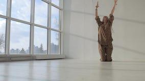 Mujer atractiva de la yoga que se sienta en las rodillas delante de ventanas almacen de video