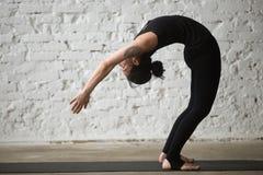 Mujer atractiva de la yogui joven en la actitud de Ardha Chakrasana, backg del desván Imagenes de archivo