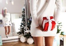 Mujer atractiva de Papá Noel con un regalo de Navidad en su mano Fotos de archivo libres de regalías