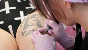 Mujer atractiva del amo del tatuaje con el cliente de los tatuajes de los dreadlocks a la muchacha en la cadera Máquina y tinta n metrajes