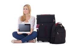 Mujer atractiva del blondie con el isolat que se sienta de la maleta y del ordenador portátil Imagen de archivo libre de regalías