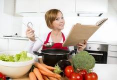 Mujer atractiva del cocinero que prepara el libro de cocina vegetal de la receta de la lectura de la sopa del guisado en la cocin Fotografía de archivo libre de regalías