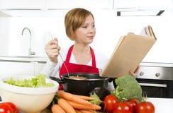 Mujer atractiva del cocinero que prepara el libro de cocina vegetal de la receta de la lectura de la sopa del guisado en la cocin Fotografía de archivo