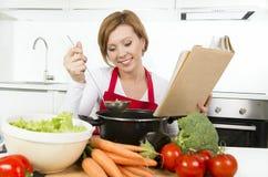Mujer atractiva del cocinero que prepara el libro de cocina vegetal de la receta de la lectura de la sopa del guisado en la cocin Fotos de archivo