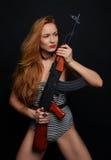 Mujer atractiva del encanto de la moda que soporta su rifle de asalto del arma g Foto de archivo