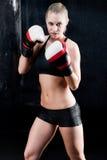 Mujer atractiva del entrenamiento del boxeo con los guantes en gimnasia Imágenes de archivo libres de regalías