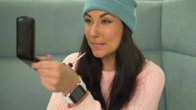 Mujer atractiva del inconformista de la raza mixta que hace maquillaje en café Lápiz labial almacen de video