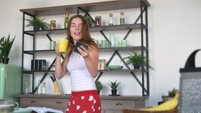 Mujer atractiva del jengibre que sostiene el teléfono y que bebe el café, bailando en cocina moderna y sonriendo, pijamas diverti metrajes