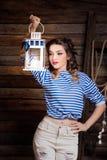 Mujer atractiva del marinero que sostiene la linterna en fondo de madera Imagen de archivo