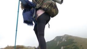 Mujer atractiva del montañés del ganador con la mochila que sube la montaña que anima después de alcanzar un pico de la cumbre - metrajes