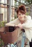 Mujer atractiva del pelirrojo con su bicicleta Imagen de archivo