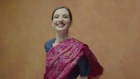 Mujer atractiva del primer en la sari alegre que hace girar almacen de video
