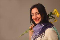 Mujer atractiva del retrato que sostiene las flores Imágenes de archivo libres de regalías