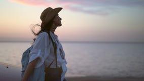 Mujer atractiva del viaje que se relaja en la puesta del sol en la playa que goza sorprendiendo el tiro medio del paisaje marino almacen de metraje de vídeo