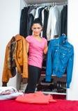 Mujer atractiva delante del armario por completo de la ropa Foto de archivo libre de regalías