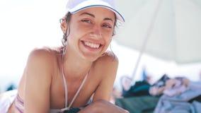 mujer atractiva delgada en el bikini y el casquillo blanco enjoing y que broncean en la playa soleada en las vacaciones de verano metrajes