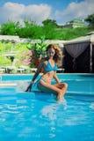 Mujer atractiva delgada hermosa cerca de la piscina de agua al aire libre en centro turístico Imágenes de archivo libres de regalías