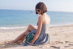 Mujer atractiva delgada joven en la playa Snakeskin hecho a mano de lujo en sus manos Foto de archivo libre de regalías