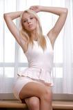 Mujer atractiva delgada joven en vestido rosado contra la ventana fotos de archivo
