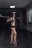Mujer atractiva deportiva hermosa que hace entrenamiento agazapado en gimnasio foto de archivo