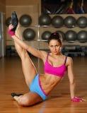 Mujer atractiva deportiva que presenta en gimnasio Foto de archivo libre de regalías
