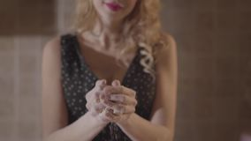 Mujer atractiva desconocida del retrato en el vestido negro manchado con pasta de mezcla de la harina en manos Cámara lenta almacen de video