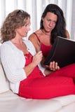 Mujer atractiva dos siiting en el sofá que discute y que toma la nota Fotografía de archivo