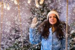 Mujer atractiva en abajo el saludo azul de la chaqueta alguien en una nieve Fotografía de archivo