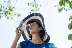 Mujer atractiva en burbujas que soplan brimmed anchas de un sunhat fotografía de archivo