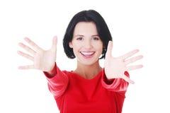 Mujer atractiva en camiseta roja con las manos abiertas. Fotos de archivo libres de regalías