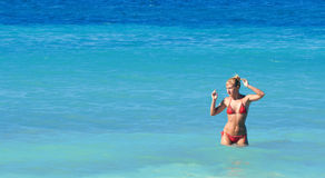 Mujer atractiva en el bikiní que presenta en un mar Foto de archivo libre de regalías