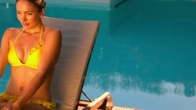 Mujer atractiva en el bikini amarillo que se relaja en poolside de la silla de cubierta metrajes